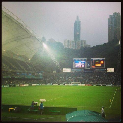 拍攝此圖時雨下得最盛,當時球場廣播宣佈首場賽事延遲半小時舉行,及後更縮短比賽時間。雖則球迷們一度鼓譟,但他們仍撐著雨傘冒雨觀賽,接近四萬人入場一睹英超列強風采可見英超以至足球運動於香港的受歡迎程度。不過如何令他們由觀賞英超轉至本土賽事才是下一個問題所在,否則每一年於香港舉辦類似賽事都無助提升本地足球水平。正如伍健先生的網誌提及,做好自己重新吸引球迷回來才是重點。當我們看著英超球星如何衝鋒陷陣時,不如想想自己可以怎樣令更多人認識甚至支持本地足球 Barclaysasiatrophy2013
