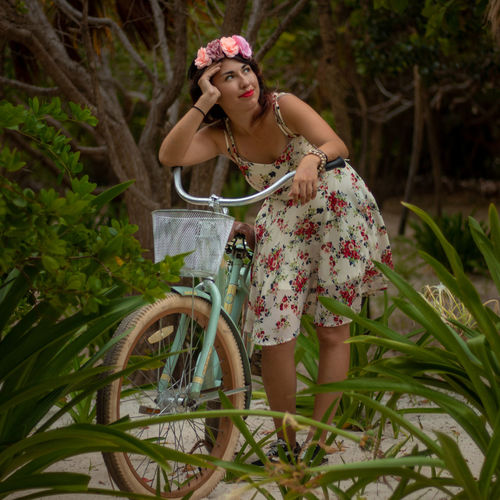 Woman with bicycle standing against plants