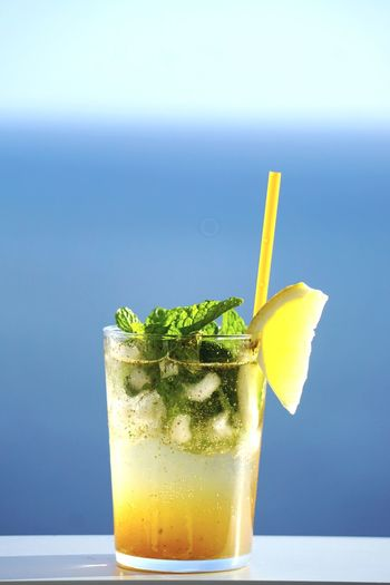 Close-up of drink on railing against sea