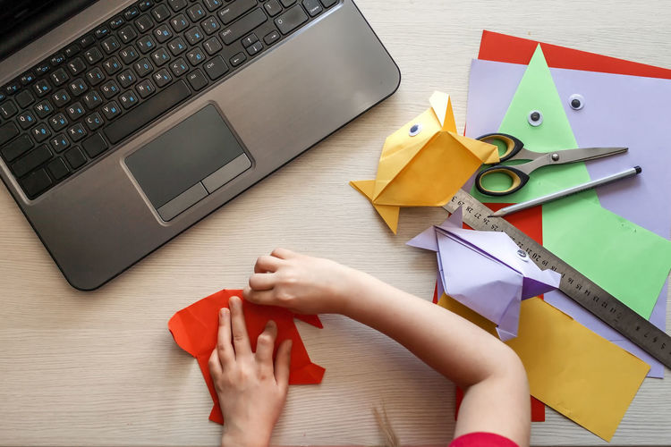 Cropped hand of girl doing origami on table