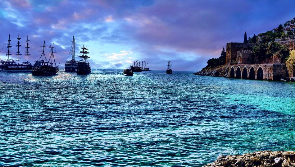 Outgoing Ships Armada Of Pirate Ships Leaving Port of Alanya Into The Light Backlit Walls Of The Old Shipyard Turkey Dramatic Sky Blue All Shades Of Blue Hdr Edit Tourist Destination Art Photography Showcase August