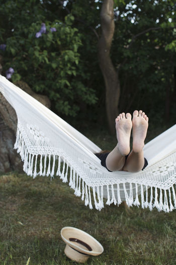 Low section of man relaxing on hammock in yard