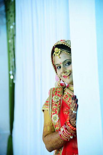 Close-up portrait of bride in sari standing against curtain