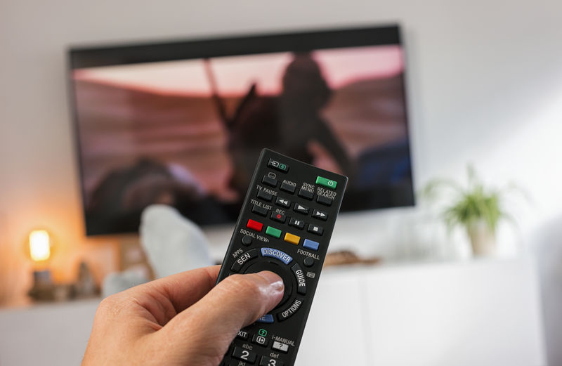 Male hand holding TV remote control and Watch 4k tv Channel Couch POV Adult Entertainment First Person View Focus On Foreground Holding Human Body Part Human Hand Living Room Movıe One Person Only Men People Program Push Button Real People Remote Control Series Sideboard Socks Technology Watching Tv Zap