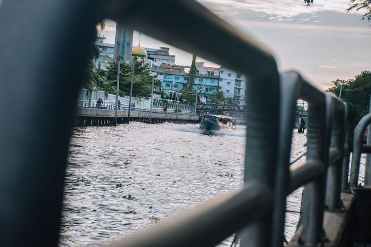 Fence by railing against sky seen through window