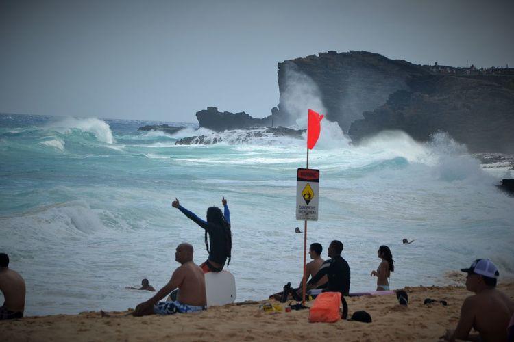 People enjoying at beach during high tide
