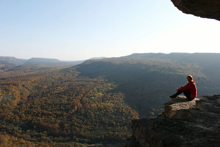Female Hiker Sitting On Cliff Against Clear Sky