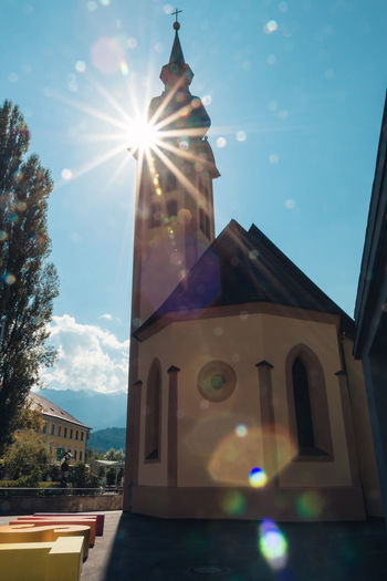 Johanneskirche in Imst. Architecture Bell Tower Building Exterior Built Structure Church City Day Johanneskirche Lens Flare Low Angle View Nature No People Nusshain 06 17 Outdoors Place Of Worship Religion Sky Spirituality Sun Sunbeam Sunlight Text Tree