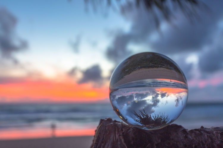 Close-up of crystal ball on sea against sky during sunset