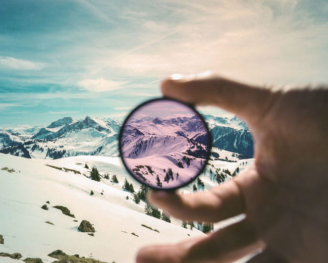 Cropped Image Of Hand Holding Circular Glass Against Snowcapped Mountains