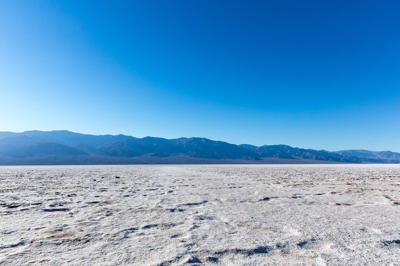 Badwater Basin Sky Scenics - Nature Blue Tranquil Scene Copy Space Mountain Tranquility Clear Sky Beauty In Nature Nature Land Day Non-urban Scene Mineral No People Environment Landscape Mountain Range Salt Flat Idyllic
