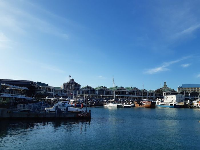 Sailboats in marina bay against blue sky