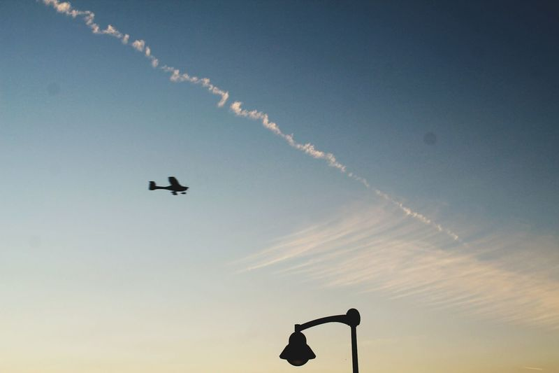 Low Angle View Flying Silhouette Vapor Trail Transportation Airplane Sunset Mode Of Transport Motion Sky Mid-air Scenics Cloud Outdoors Carefree Air Vehicle Lamp Post Lighting Equipment Street Light Transportation TakeoverContrast Backlight Contraluz