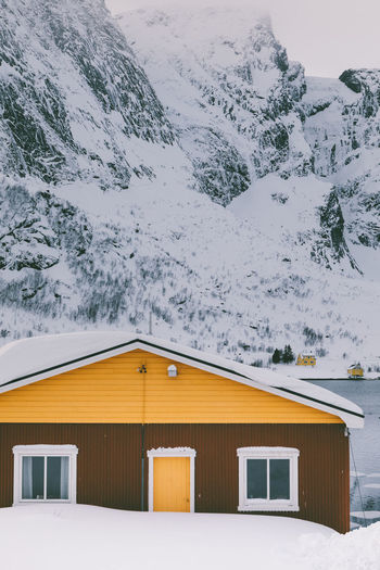 Snow covered house by building against sky