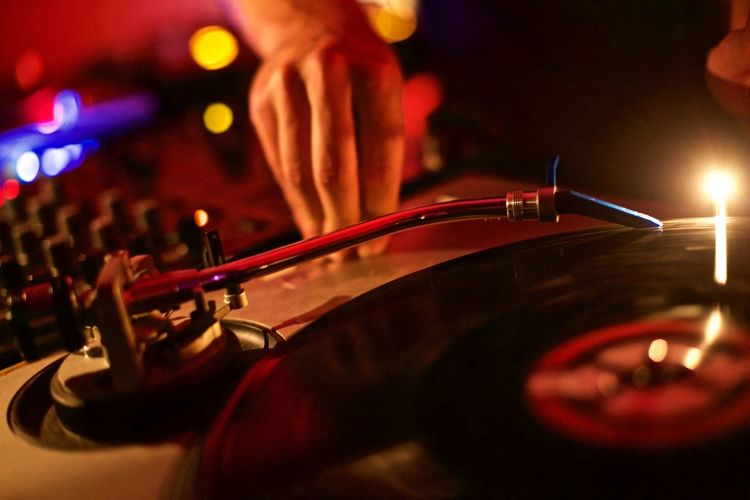 Cropped image of dj playing music at turntable