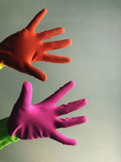 Cropped hands of person wearing gloves against wall