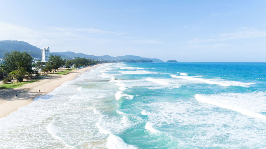 Aquatic Sport Beach Beauty In Nature Day Horizon Over Water Idyllic Land Motion Mountain Nature Outdoors Power In Nature Scenics - Nature Sea Sky Sport Surfing Tree Water Wave