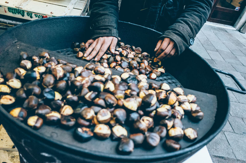 Midsection of person selling roasted chestnut at street