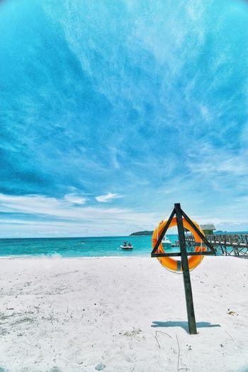 Life belt at beach against cloudy blue sky