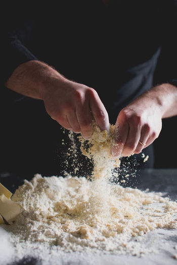 CROPPED VIEW OF CHEF'S HANDS KNEADING PASTRY