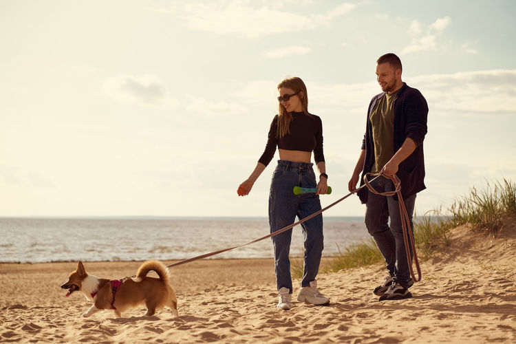 Young happy couple and dog standing along beach. man with woman looking away and holding corgi