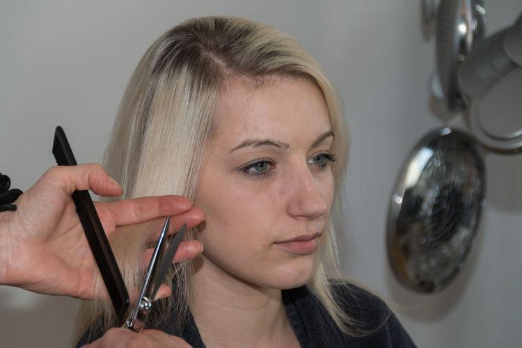 Hairdresser cutting woman hair at salon