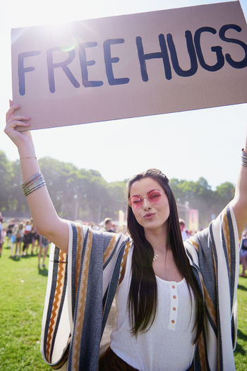 Portrait of young woman holding up free hug sign at festival Free Hugs Woman Embrace Festival Music Festival Traditional Festival Boho Hippy Fun Playful Portrait Hand Raised Coachella Valley Entertainment Party Music Summer Outdoors Freedom Carefree Traveling Carnival Celebration Holiday Youth Culture Hold Up Cardboard Hug Popular Music Concert Vacations Sunglasses Fashion Fashionable Adult Young Adult Happiness Enjoyment Joy Live Event Look At Camera