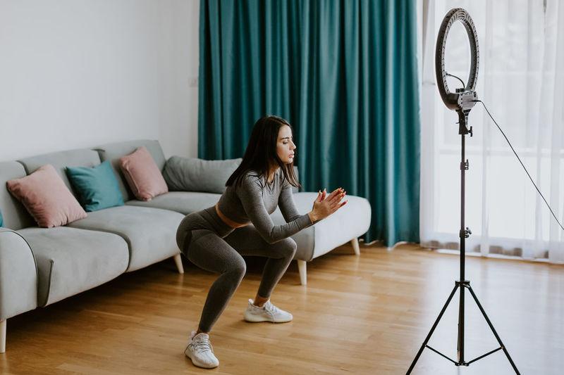 Full length of woman sitting on hardwood floor at home