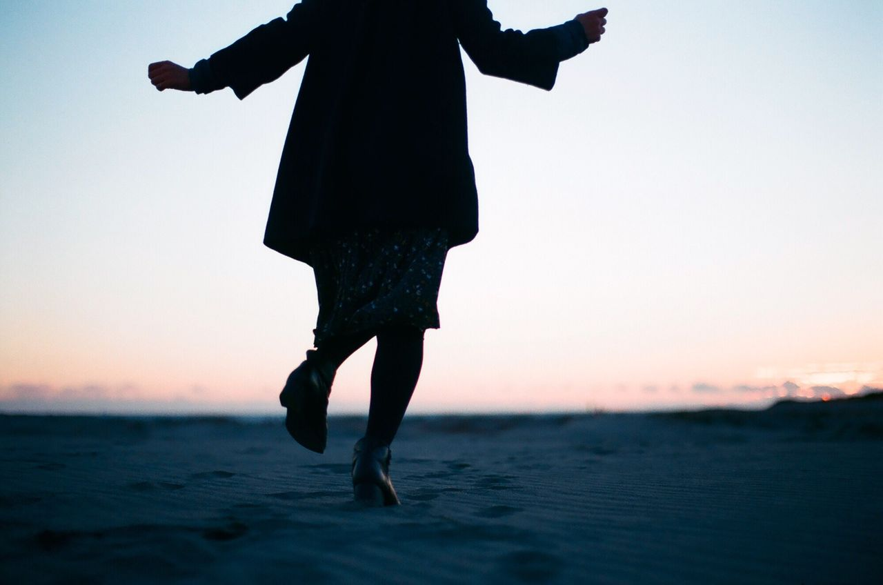 Low Section Of Woman With Arms Outstretched Running At Beach During Sunset