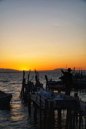 Silhouette boats moored on sea against orange sky