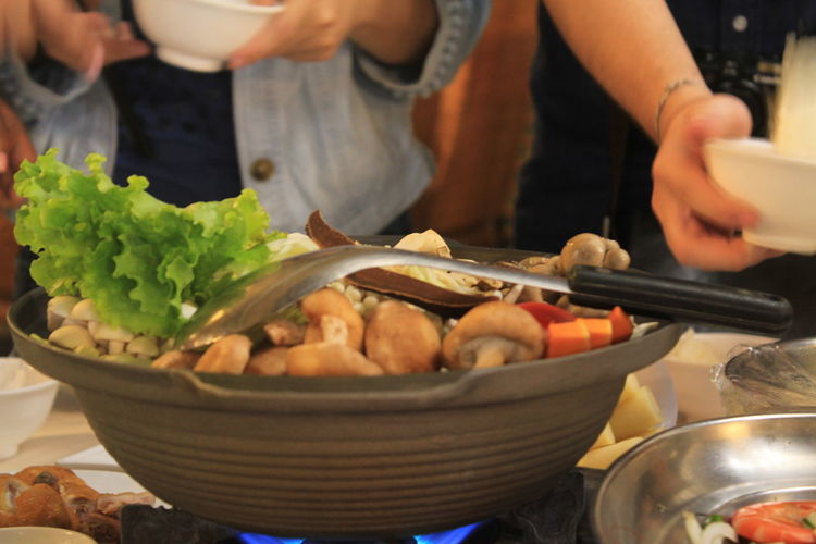Midsection of people standing by bowl with food