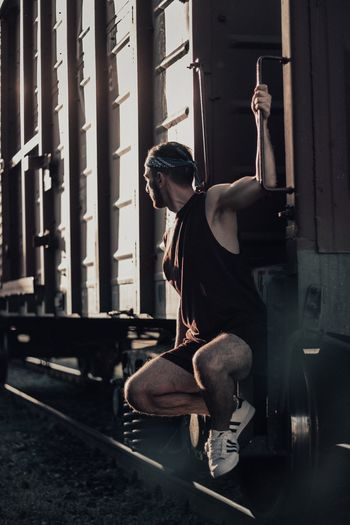 Young man sitting on cargo train