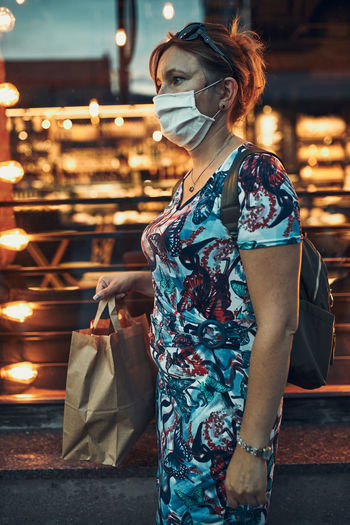 Young woman walking along a store front after shopping in the city center in the evening