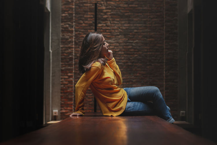 Woman sitting on wall at home