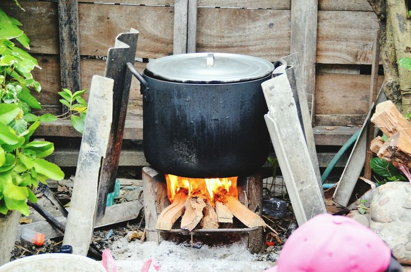 Food being prepared in container over wood burning stove