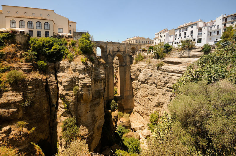 Spain, Andalusia, Ronda. Landscape with new bridge. Ancient Ancient Civilization Archaeology Architectural Column Architecture Building Building Exterior Built Structure Clear Sky Day History Nature No People Old Old Ruin Outdoors Plant Ruined Sky Sunlight The Past Travel Travel Destinations Tree