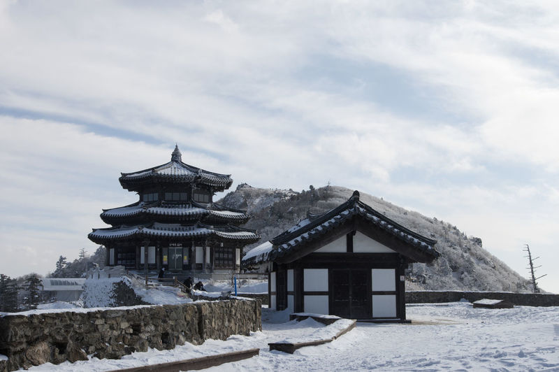 Historical building on snow covered landscape against cloudy sky