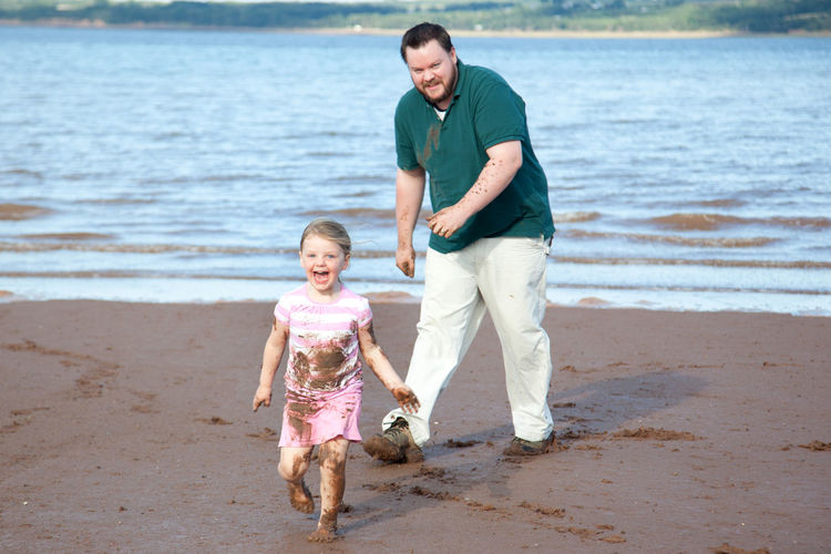 Daughter playing with father at beach