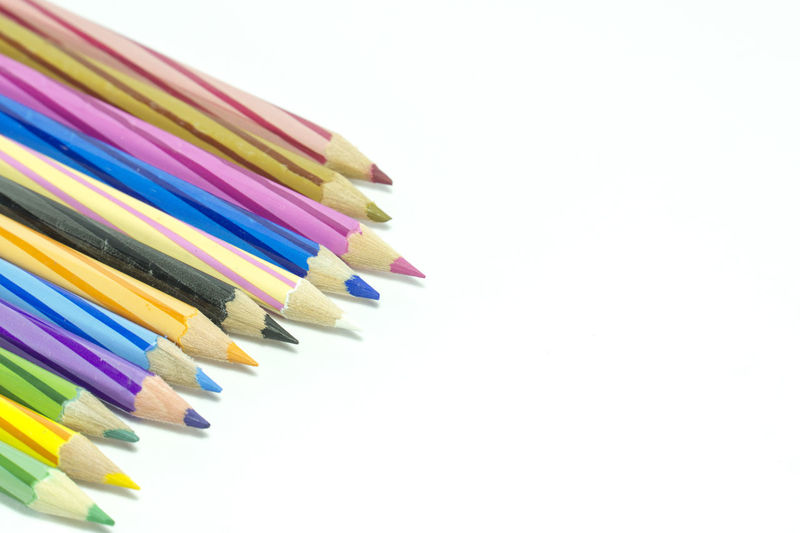 Close-up of colored pencils over white background