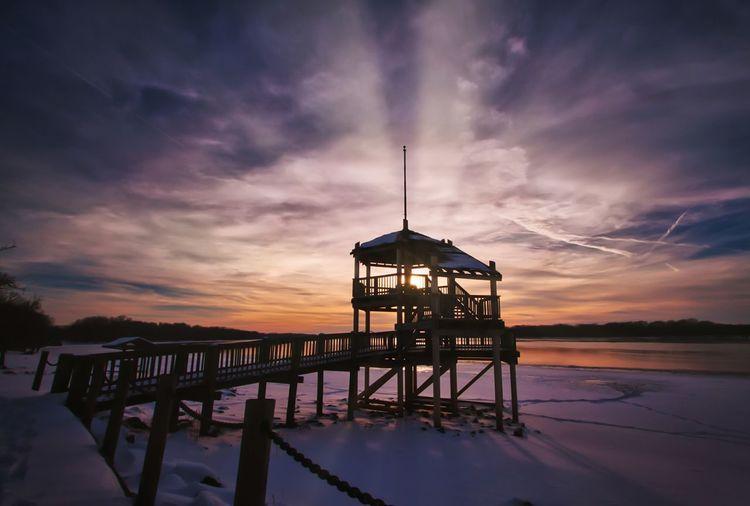 Gazebo at beach against sky during sunset