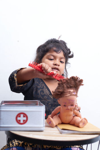 Cute girl combing hair of doll while sitting against white background