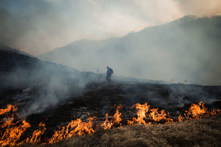 Man standing by bonfire on mountain against sky