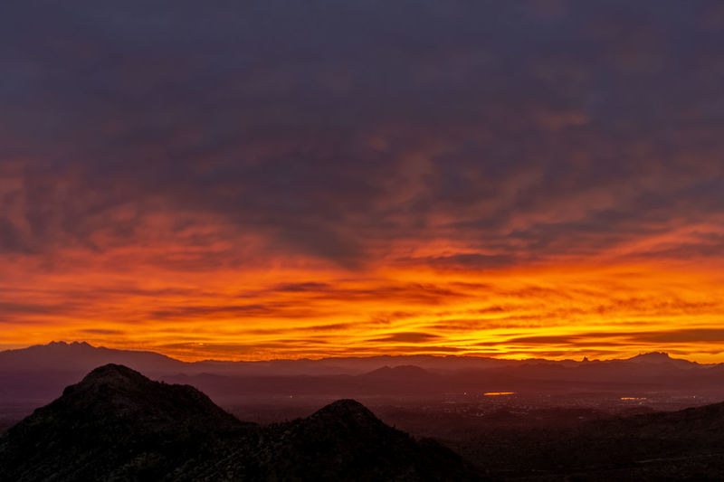 Scenic view of dramatic sky over silhouette mountains during sunset