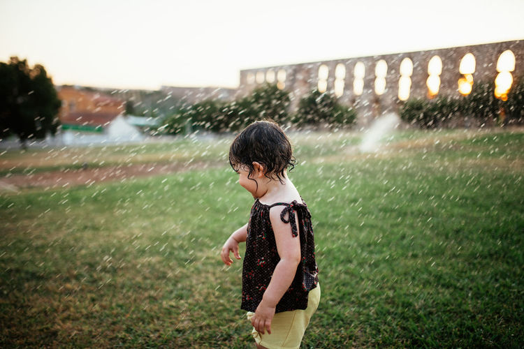 Full length of child playing with water sprinklers