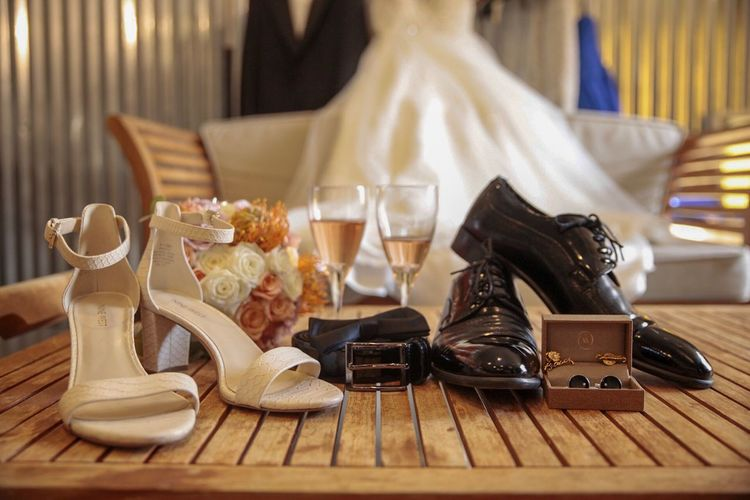 Close-up of personal accessories with drinks on table at wedding ceremony