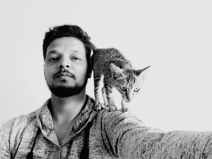 Portrait of man with cat against white background
