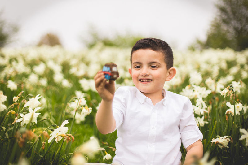 Portrait of cute boy holding a toy on field