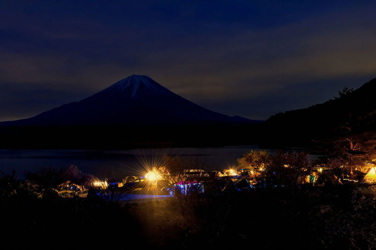 Illuminated mountain by lake against sky at night