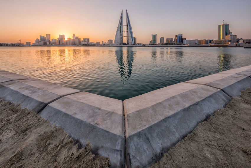 MANAMA, BAHRAIN - OCT 28, 2016: Beautiful view of the Seafront with illuminated World Trade Center and other high rise buildings in the city. Bahrain WTC Architecture Building Building Exterior Built Structure City Cityscape Digital Composite Landscape Modern Nature No People Office Building Exterior Outdoors Reflection River Skyscraper Sunset Tall - High Tower Travel Destinations Twin Towers Urban Skyline Water