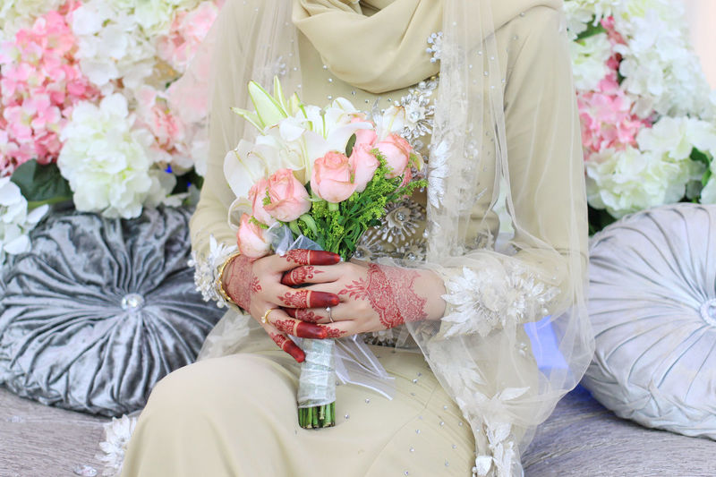 Midsection Of Bride With Bouquet Sitting On Sofa During Wedding